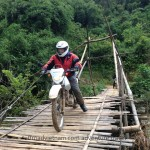 Vietnam motorcycle tours over a local bamboo bridge in rainy season