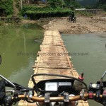 Vietnam enduro tours over a local bamboo bridge in rainy season